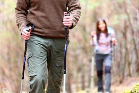 couples outdoors: Hiking. Closeup of hiker detail showing hiking poles. Hikers walking in autumn forest.