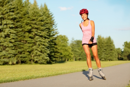 rollerblading: Roller skating girl in park rollerblading on inline skates. Mixed race Asian Chinese  Caucasian woman in outdoor activities. Stock Photo
