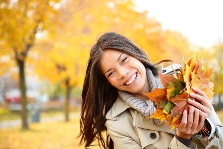people laughing: Autumn girl playing in city park. Fall woman portrait of happy lovely and beautiful mixed race Asian Caucasian young woman in forest in fall colors.