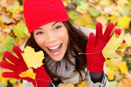 Happy autumn woman playing in leaves. utumn portrait of happy lovely and beautiful mixed race Asian Caucasian young woman in forest in fall colors. photo