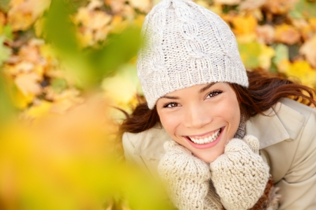 mixed colors: Autumn woman in yellow leaves portrait. utumn portrait of happy lovely and beautiful mixed race Asian Caucasian young woman in forest in fall colors.
