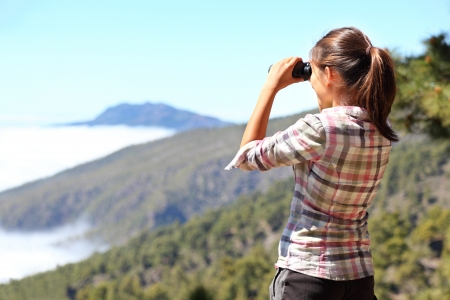 bird watcher: Hiker looking in binoculars enjoying view above clouds during hiking trip. Young Asian woman on hike on La Palma, Canary Islands, Spain.