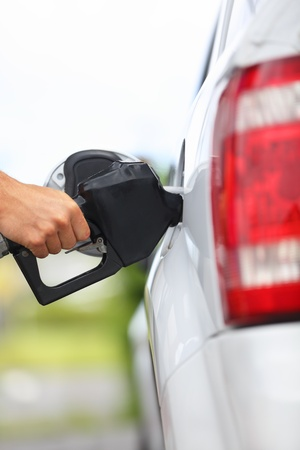 benzin: Gas station pump. Man filling gasoline fuel in car holding nozzle. Close up.