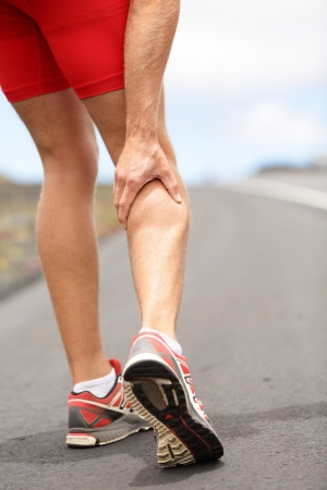 aching muscles: Cramps in leg calves or sprain calf on ttriathlete runner  Sports injury concept with running man