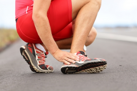 Broken twisted angle - running sport injury Male runner touching foot in pain due to sprained ankle