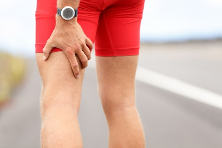 Hamstring sprain or cramps  Running sports injury with male triathlete runner  photo
