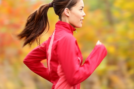 Running in Fall  Runner woman jogging in autumn forest  Beautiful young fit fitness sport model jogging with slight motion blur  Mixed race Caucasian   Asian girl  Stock Photo