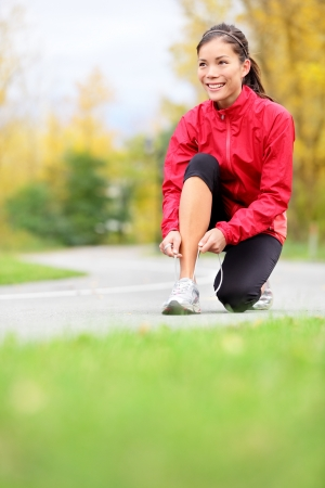 Runner woman tying running shoes outside in fall  Beautiful young fitness model smiling happy in casual jogging clothing  photo