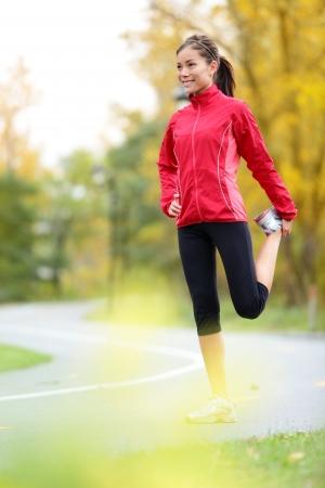 растягивание: Runner женщина растяжения бедра после запуска в городе лесопарка в падении Красивый молодой смешанной расы кавказских азиатских женщин модель фитнеса в цвет осени Фото со стока