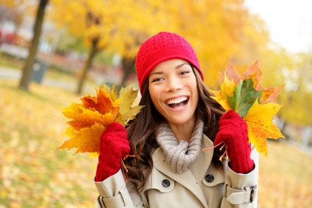 blissful: Fall woman happy and bliss in autumn city forest park holding colorful fall leaves smiling happy and joyful wearing tuque and knit gloves  Pretty multiracial Asian and Caucasian girl model
