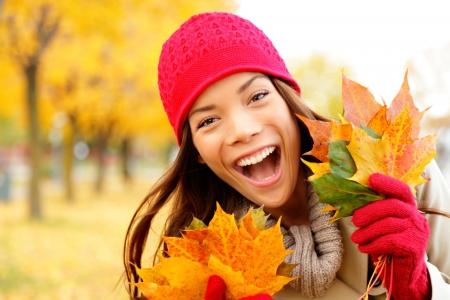 Opgewonden gelukkige val vrouw die lacht vreugdevol en gelukzalig bezit herfstbladeren buiten in de kleurrijke herfst bos Mooie energieke gemengd ras Kaukasische Aziatische Chinese jonge vrouw Stockfoto