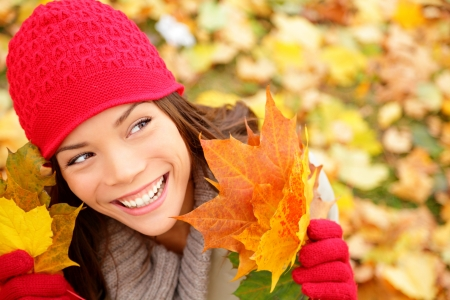 Fall woman looking at copy space holding fall leaves smiling happy and joyful  Lovely beautiful girl wearing red knit hat and gloves  Fall lifestyle concept image