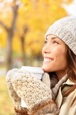 tomando café: Otoño mujer bebiendo café concepto Otoño de la mujer joven que disfruta de la bebida caliente de la taza de café desechables al aire libre en el paisaje de otoño sereno contento modelo mixto raza caucásica mujer asiática en otoño en el parque forestal de la ciudad