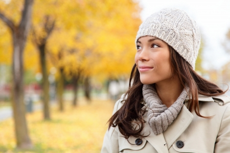 Fall woman portrait of woman looking sideways smiling serene  Beautiful young multiracial woman walking in autumn in city forest park in trench coat  photo