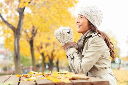 trench: Fall concept - autumn woman drinking coffee on park bench under fall foliage  Beautiful young modern woman smiling happy and cheerful in trench coat  Stock Photo