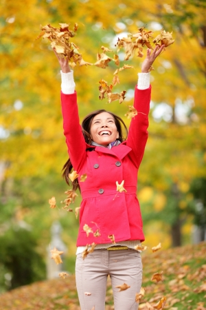 blissful: Happy fall woman throwing autumn leaves up in the air smiling blissful and cheerful in autumn forest  Young beautiful multicultural Caucasian   Asian woman model outside  Stock Photo