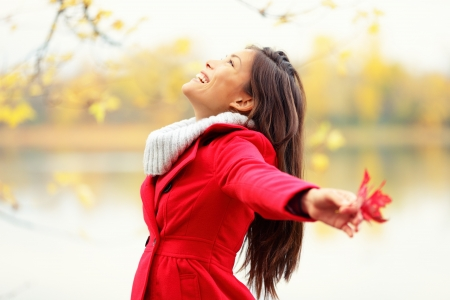 blissful: Happy autumn woman blissful and playful smiling with arms out holding red fall leave by lake