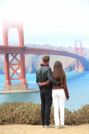 couples outdoors: San Francisco Golden Gate Bridge  Young traveling couple enjoying view of the travel icon landmark and San Francisco Bay