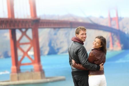 persona viajando: El Golden Gate Bridge pareja feliz de viajes en San Francisco, EE.UU. sonriendo a la c�mara Pareja joven inconformista interracial disfrutando de la vista en el hito famoso del recorrido Foto de archivo