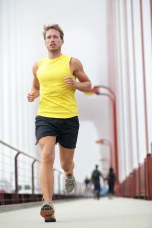 Fit running außerhalb Junge männliche Fitness-Modell Ausbildung in gelb auf Golden Gate Bridge, San Francisco, California, USA