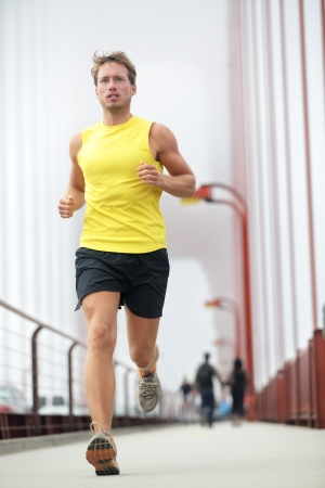 hacer footing: Montar running fuera joven modelo de fitness masculino formaci�n en amarillo sobre Golden Gate Bridge, San Francisco, California, EE.UU.
