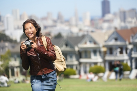 Alamo Square San Francisco Tourist  Young traveler woman holding camera taking tourist photo in Alamo Park by the Painted Ladies, The Seven Sisters, San Francisco, California, USA  Beautiful happy smiling multicultural woman  Stock Photo