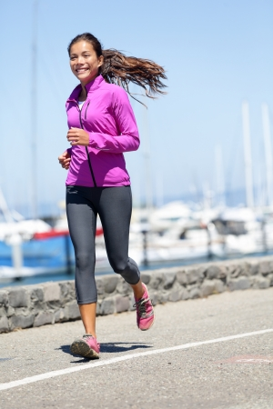 Woman running in fall   autumn running clothing outfit  Smiling happy female athlete runner training on waterfront harbour pier in San Francisco, California, USA  Mixed race fit fitness sport model  photo