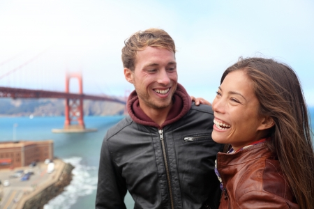 san francisco bay: Happy young couple laughing in San Francisco by Golden Gate Bridge  Interracial young modern couple, Asian woman, Caucasian man  Stock Photo