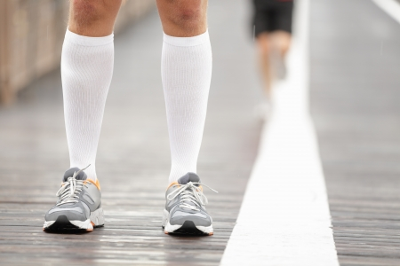 men socks: Running shoes closeup and compression socks on male runner. Closeup of runners feet on Brooklyn Bridge, New York City. Stock Photo
