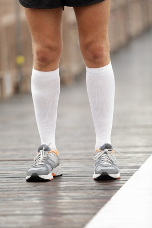 compression: Running shoes and compression socks on male runner. Closeup of runners feet on Brooklyn Bridge, New York City.