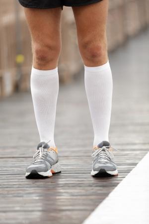 calcetines: Zapatillas y calcetines de compresi�n en corredor masculino. Primer plano de los pies de los corredores sobre el Brooklyn Bridge, New York City. Foto de archivo