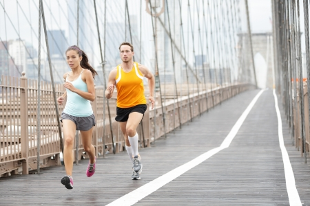 couple in rain: Running couple. Runners training outside. Asian woman and Caucasian man runner and fitness sport models jogging in full body showing Brooklyn Bridge, New York City, USA.