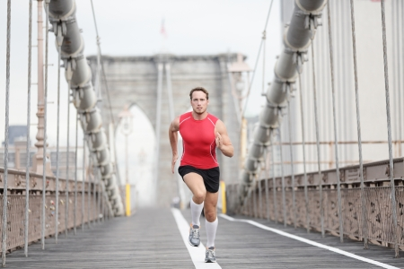 brooklyn: Running runner man sprinting at speed. Male athlete training alone in full body wearing red compression top and socks during run on Brooklyn Bridge, New York City, USA. Stock Photo
