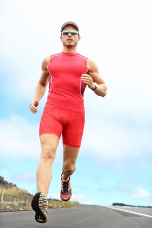 triathlon: Triathlon running man. Triathlete runner training on Hawaii for ironman. Male athlete running in red compression clothing, shorts and top on volcano on Big Island, Hawaii.