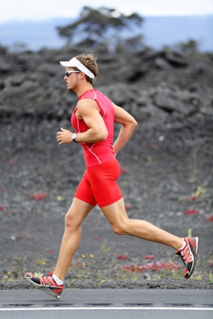 ironman: Triathlon runner man. Triathlete running training on Hawaii for ironman. Male athlete running in red compression clothing, shorts and top on volcano on Big Island, Hawaii. Stock Photo