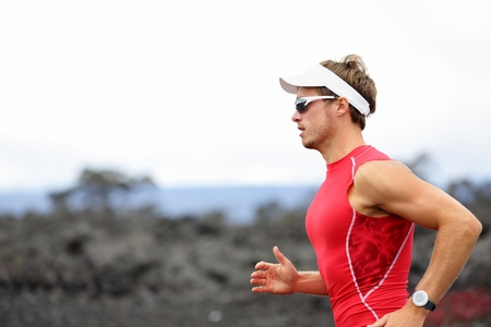 ironman: Running triathlon athlete man. Runner triathlete training for ironman on Hawaii. Young Male athlete running in red compression top on volcano in Kailua-Kona, Big Island, Hawaii. Stock Photo