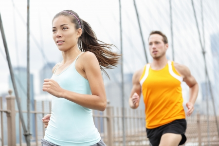 Running couple. Woman and man runner athletes training outside for marathon. Photo from Brooklyn Bridge, New York City, USA. Asian woman and Caucasian man fitness sport models. 版權商用圖片