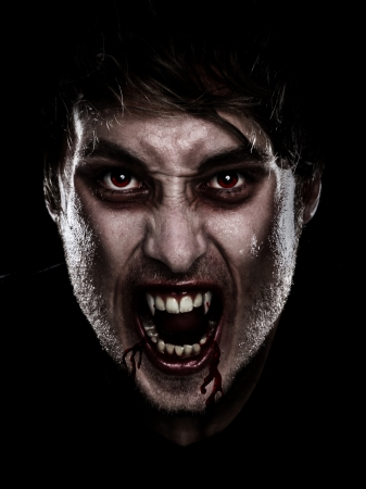 fangs: Vampire halloween man. Portrait of blood thirsty vampire man with blood dripping fangs - closeup. Stock Photo