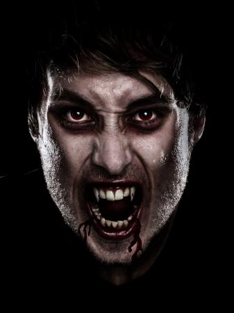 vampire teeth: Vampire halloween man. Portrait of blood thirsty vampire man with blood dripping fangs - closeup. Stock Photo