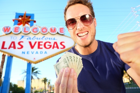 las vegas strip: Las Vegas man winning money. Winning gambler standing excited in front of Welcome to Fabulous Las Vegas sign.