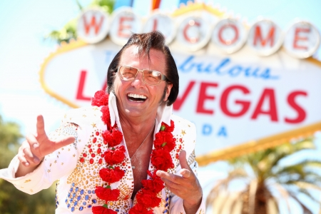 Las Vegas Elvis impersonator laughing having fun in front of Welcome to Fabulous Las Vegas sign. photo