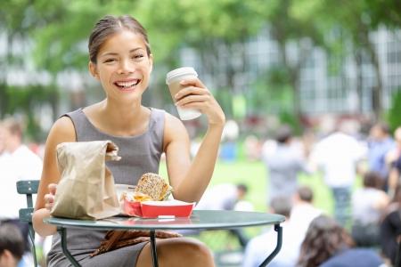 tomando café: Mujer de negocios joven en la hora del almuerzo en el café para beber City Park y comiendo sándwich Foto de archivo