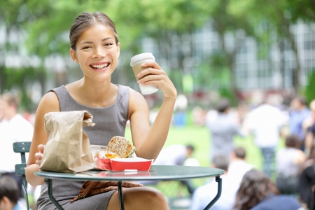 eating: Young business woman on lunch break in City Park drinking coffee and eating sandwich