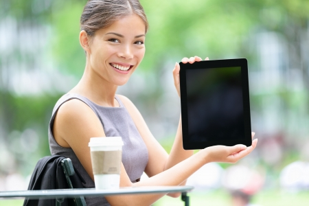 bryant: Tablet business woman showing display screen sitting in park