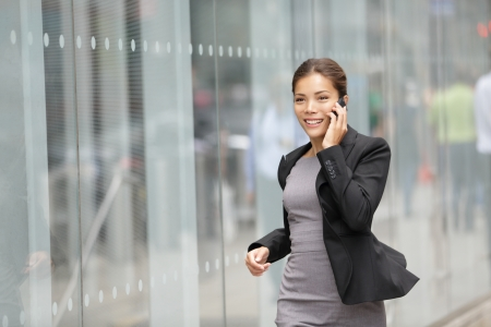 running late: Businesswoman on cellphone running while talking on smart phone Stock Photo
