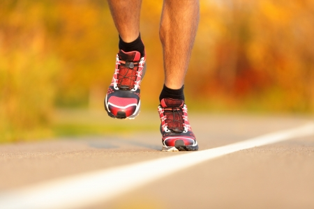 closeup on legs: Athlete running shoes close-up  Man runner jogging outdoors in fall Stock Photo
