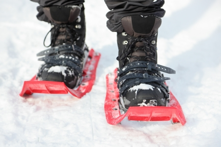 highend: Snowshoes  Snowshoeing closeup  Red new modern high-end snowshoes  Man hiking in snow on snowy winter day