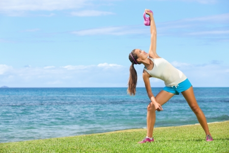 Crossfit exercise woman using kettlebell in fitness strength training workout outside on grass by the ocean. Beautiful young fit instructor and fitness model. photo