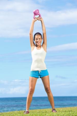 kettles: Fitness mujer crossfit ejercicio al aire libre con pesas rusas en entrenamiento cruzado. Gimnasio modelo e instructor mostrando dos basculante kettlebell.