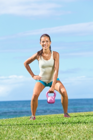 kettles: Crossfit fitness exercise woman lifting kettlebell during strength training exercising outdoors on grass by the ocean. Beautiful young fit fitness instructor doing one-arm kettlebell swing or snatch.